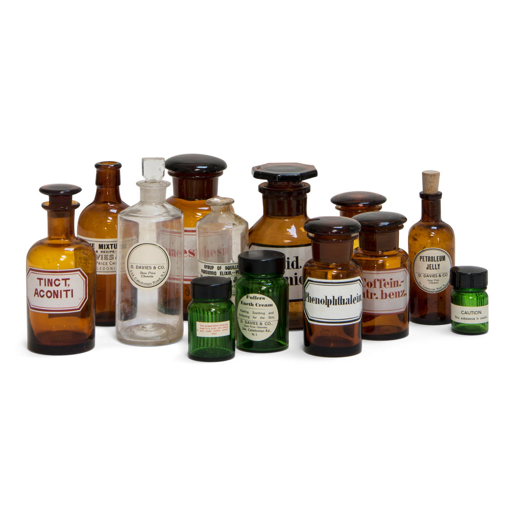 A large collection of early twentieth century pharmacy bottles, in amber, clear and green glass. There are 13 in in total and all are with their original labels - some are from D Davies & Co, Caledonian Road, London N1.