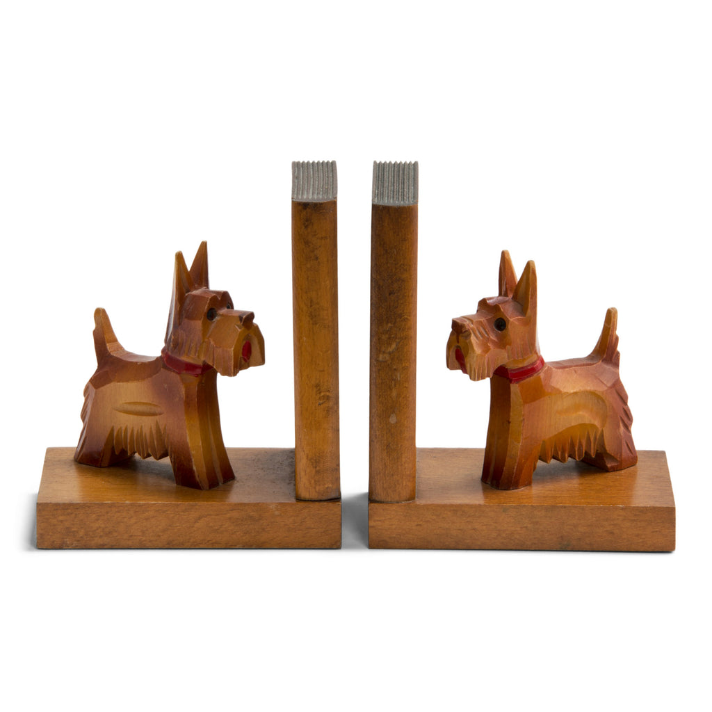 A charming pair of 1930s carved wood scottie dog bookends. Each dog has a painted red collar and tongue, and is mounted on an oak platform with an oak support modelled as a book. Scottie dogs were all the rage in the 1930s: as pets with box-clipped muzzles; as stylised Art Deco Bakelite brooches and clasps; adorning greetings and postcards; as ornaments, modelled in china, metal and wood; and as bookends - such as this dear little pair.