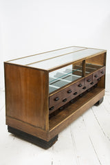A rare high quality 1930s Art Deco shop counter fitted with eighteen Bakelite display drawers and brass frame to its vitrine. It has oak veneer panelled sides and front with black painted Art Deco stepped feet mounted on ball castors – so it can be moved with absolute ease.  The maker and shopfitters nameplate 'Courtney Pope Ltd of London N15' is secured to the inside front of the cabinet, and each Bakelite drawer is beautifully monogrammed with the initials CP in a striking 1930s modernist font.