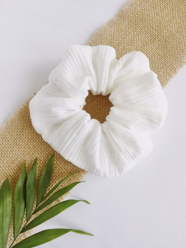 White wrinkled large scrunchies placed on a brown and white background