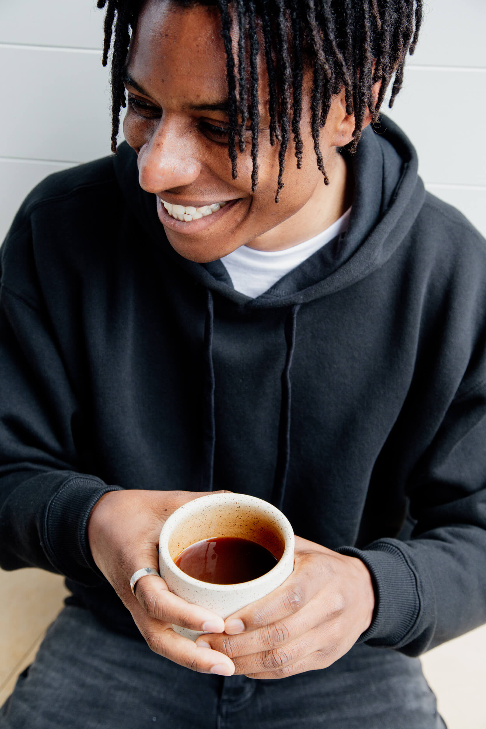 Man drinking coffee in a product photo for Citizen Clothing in Victoria BC.