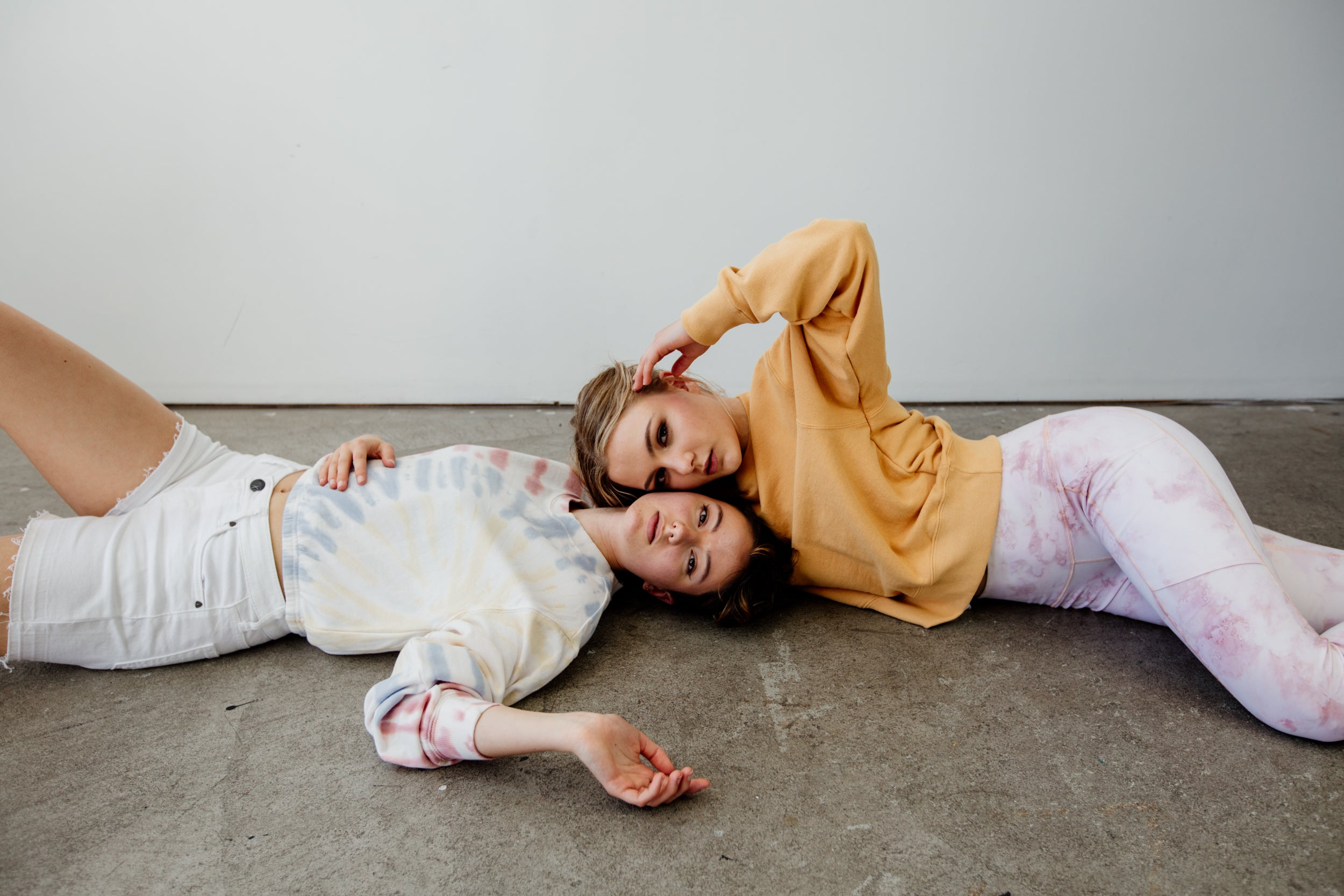 Two women lie on the floor