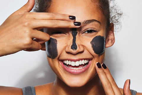 Black woman smiling and applying a face mask