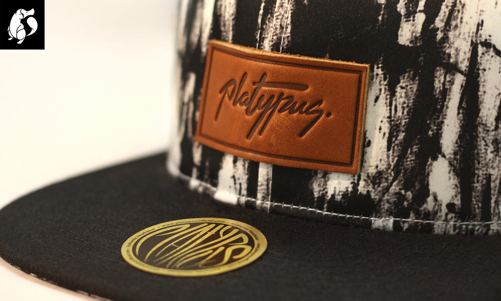 Close up of charcoal arty crown snapback cap and leather Platypus patch