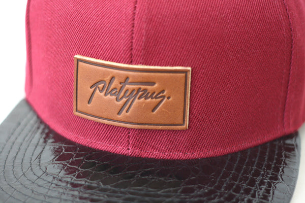 Close up of Platypus Burgundy and Snakeskin Style Snapback Hat with leather patch