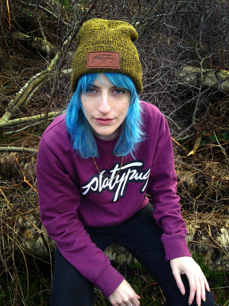Model wearing Antique Mustard beanie with Plum Platypus logo crewneck sweatshirt.