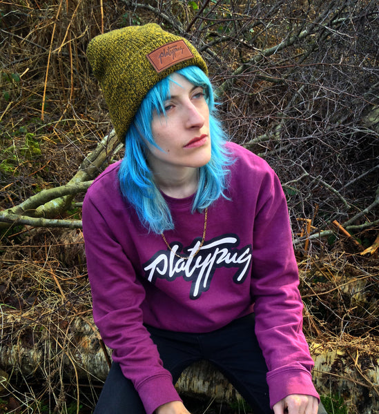 Model wearing Platypus Logo Urban Sweatshirt jumper in Plum and mustard Beanie