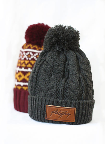 Platypus Charcoal Cable Knit Beanie in front of Pattern burgundy beanie