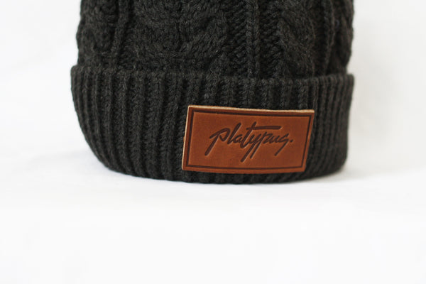 Close up of leather Platypus logo on Charcoal Cable Knitted Beanie
