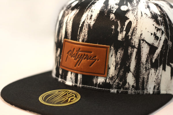Close up of Platypus Clothing's Leather Signature Charcoal Pattern Snapback Cap