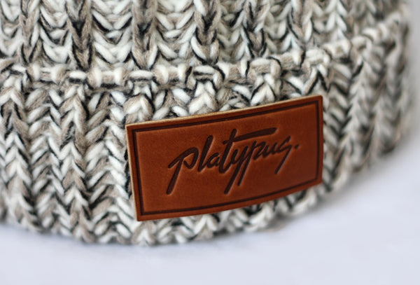 Close up of leather Platypus logo on Oatmeal Knit beanie