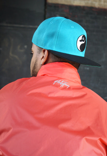 Close up of embroidered detail on coral platypus parka jacket with Yin yang snapback.