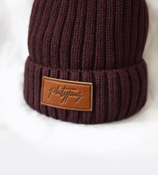 Close up of Platypus leather logo Plum Beanie