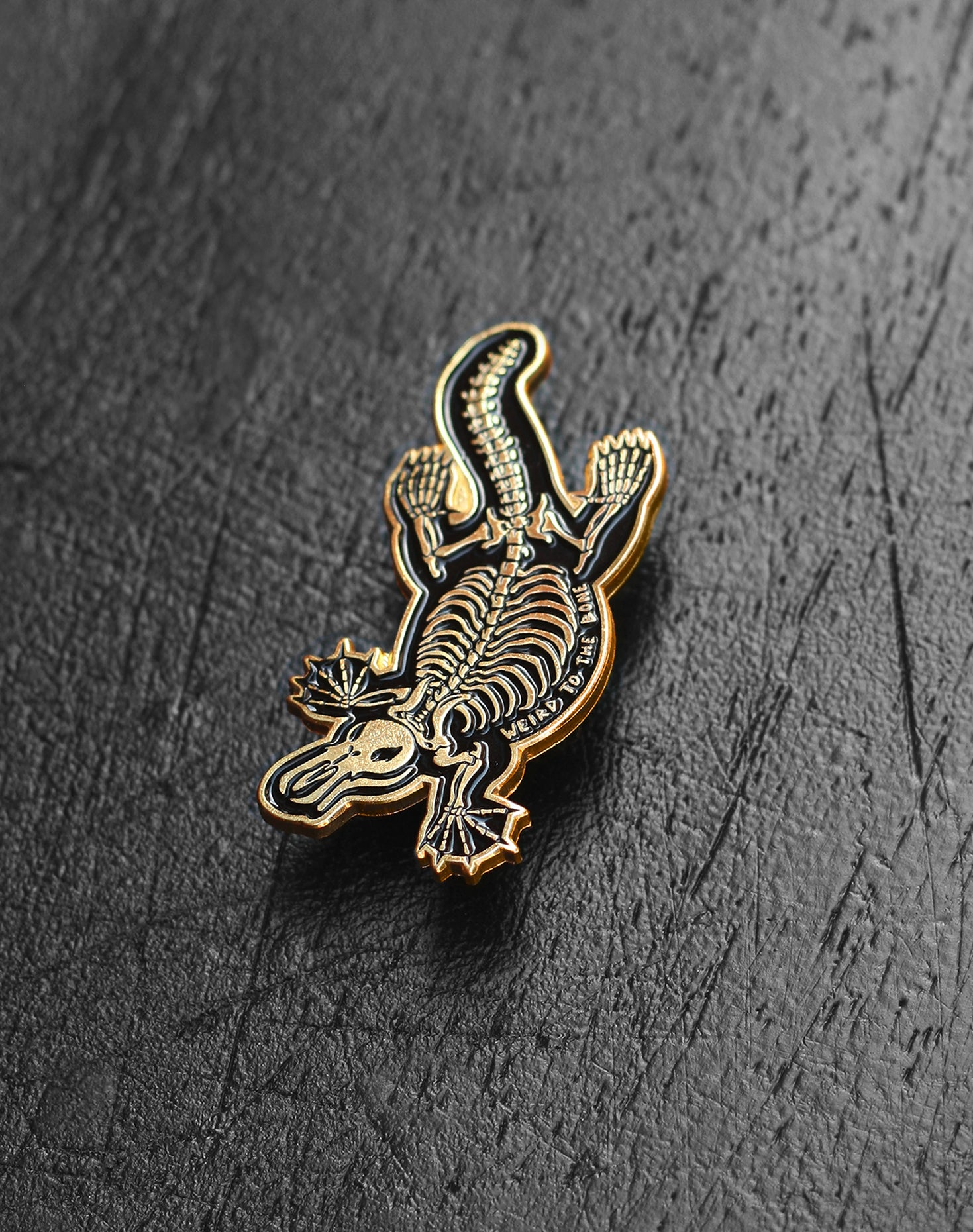 """Weird To The Bone"" Gold Skeleton Platypus Enamel Pin"