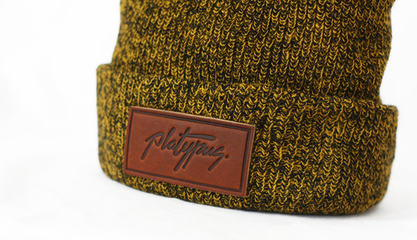 Close up of Platypus leather logo patch on Antique Mustard beanie