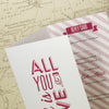 Close Up of 'All You Need' Ivory Tri-Fold Wedding Invitation