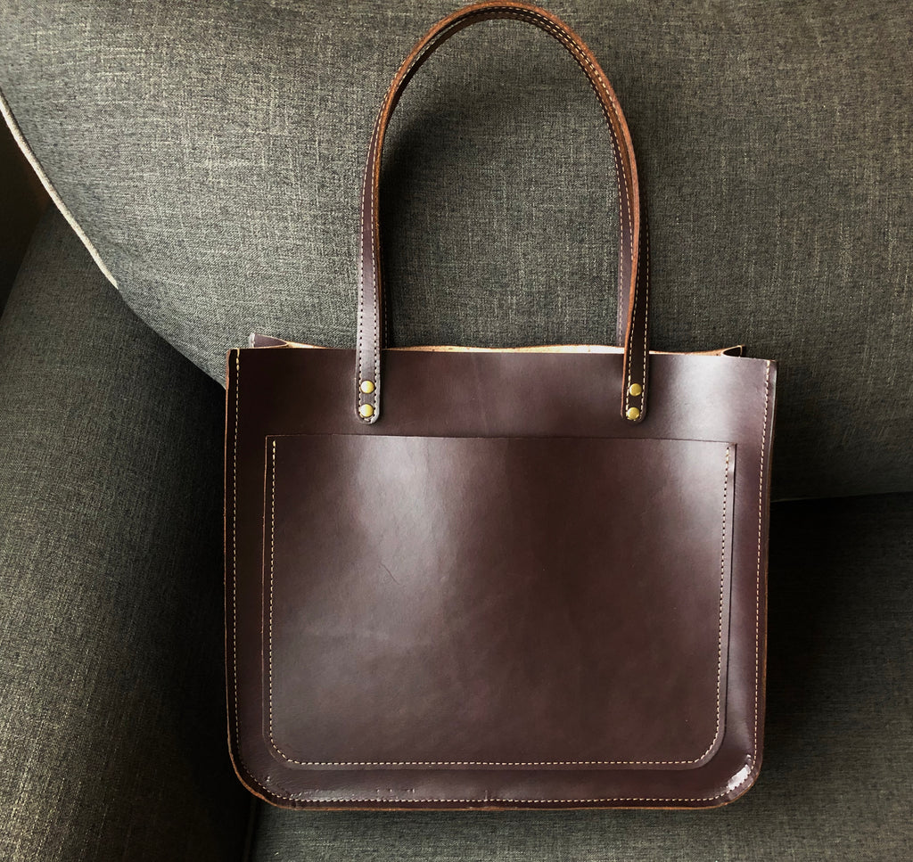 Rich brown leather tote bag sits on couch.