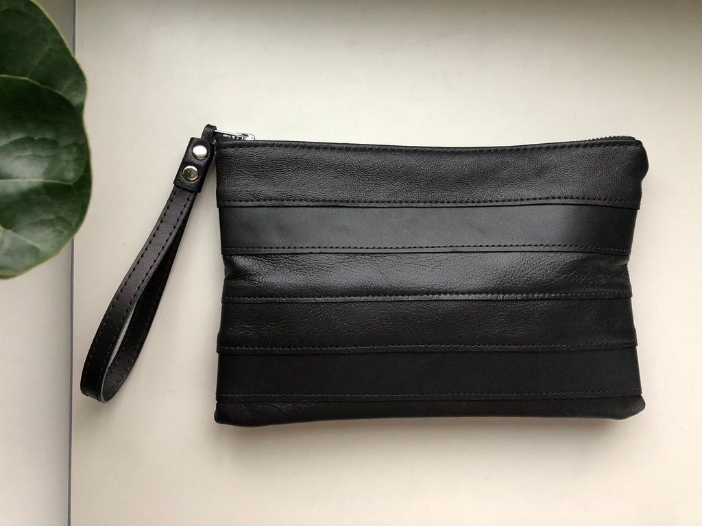Strips of black leather form this elegant little clutch with wrist strap.