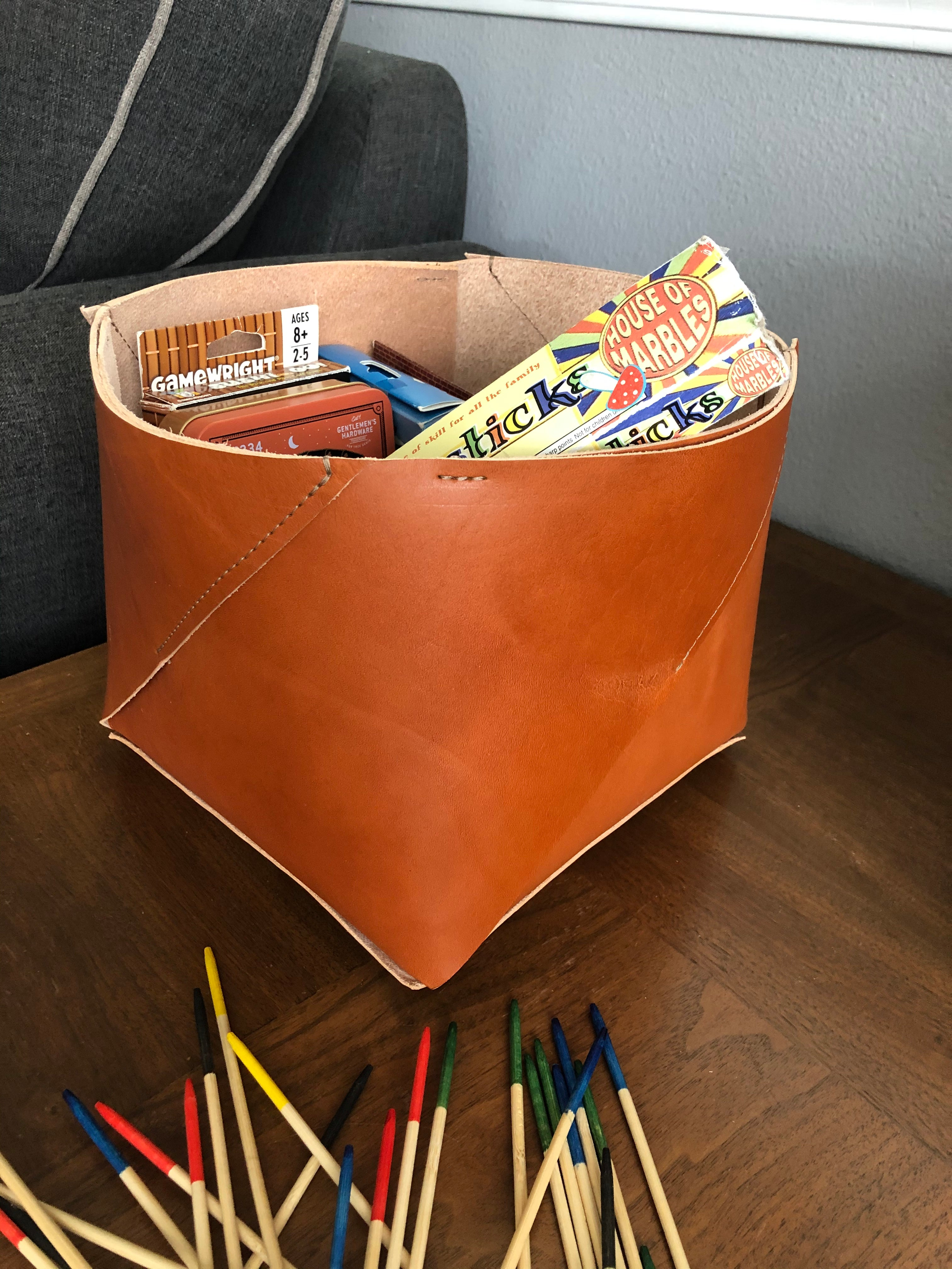 Modern leather bin holds an assortment of games.