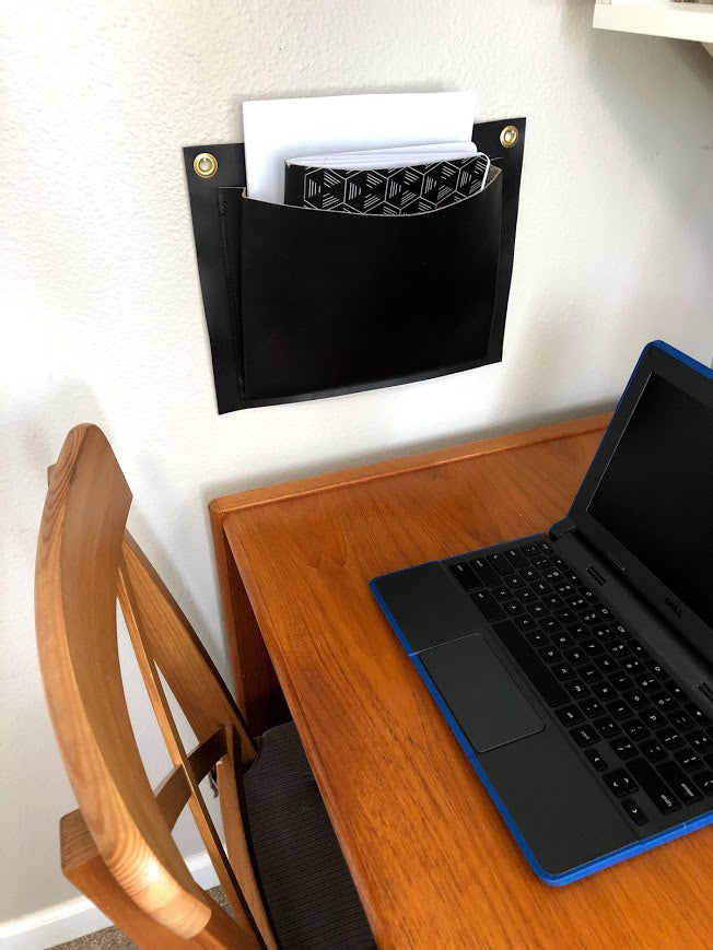Black leather wall pocket hangs above desk and computer.