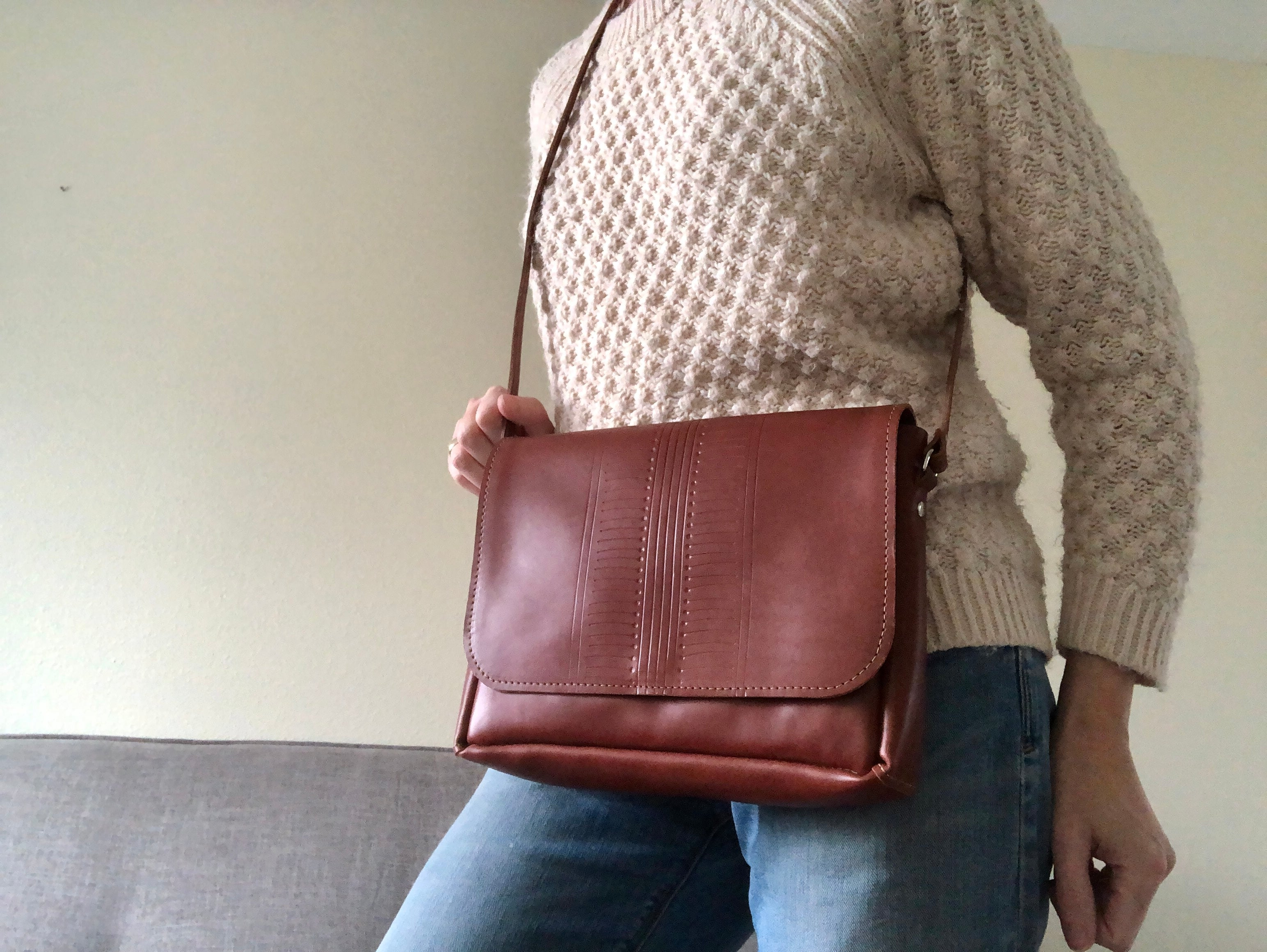 Woman wears brown leather bag with center pattern detail.