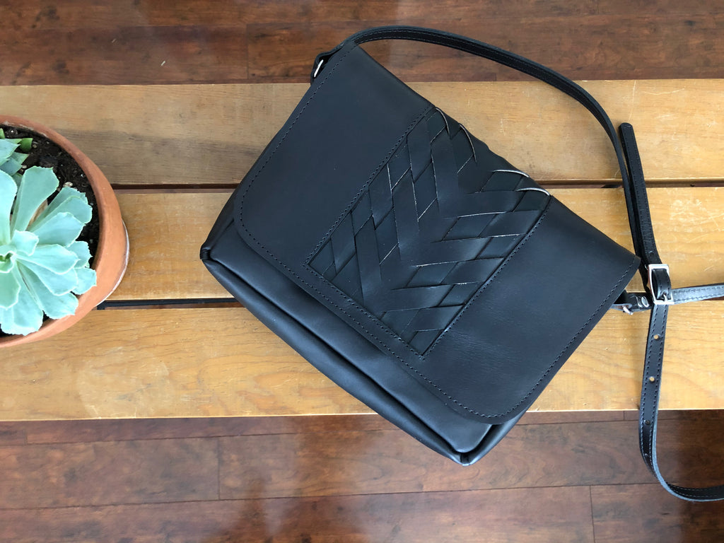 Black leather crossbody bag with woven center panel, lies on wooden table.