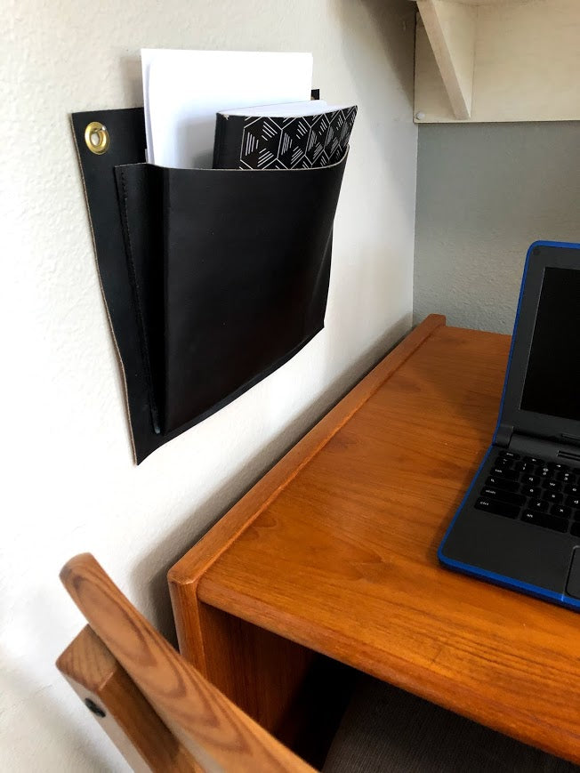 Black leather wall pocket hangs above wooden desk