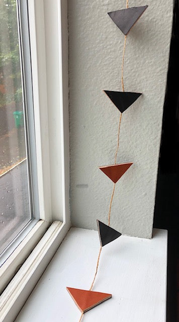 Black and orange triangle leather garland decorates a window