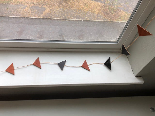 Fall leather garland decorates a window sill.
