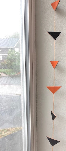 Black and orange triangle garland hangs in window