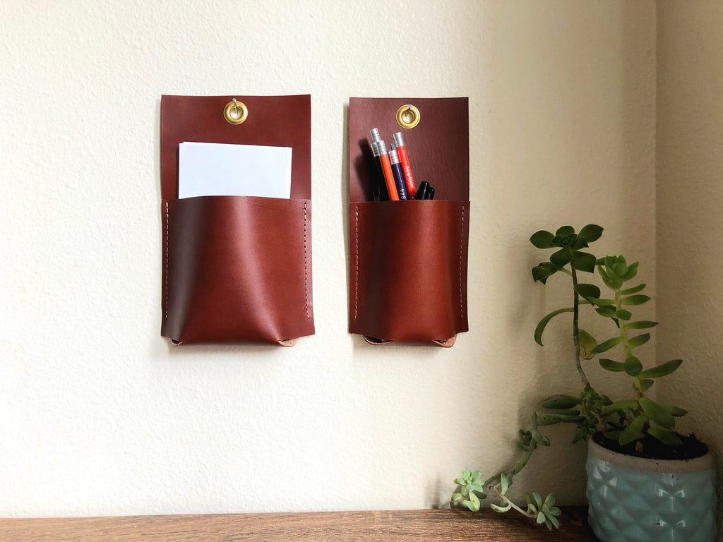 Two brown leather wall pockets hang together holding pencils and paper.