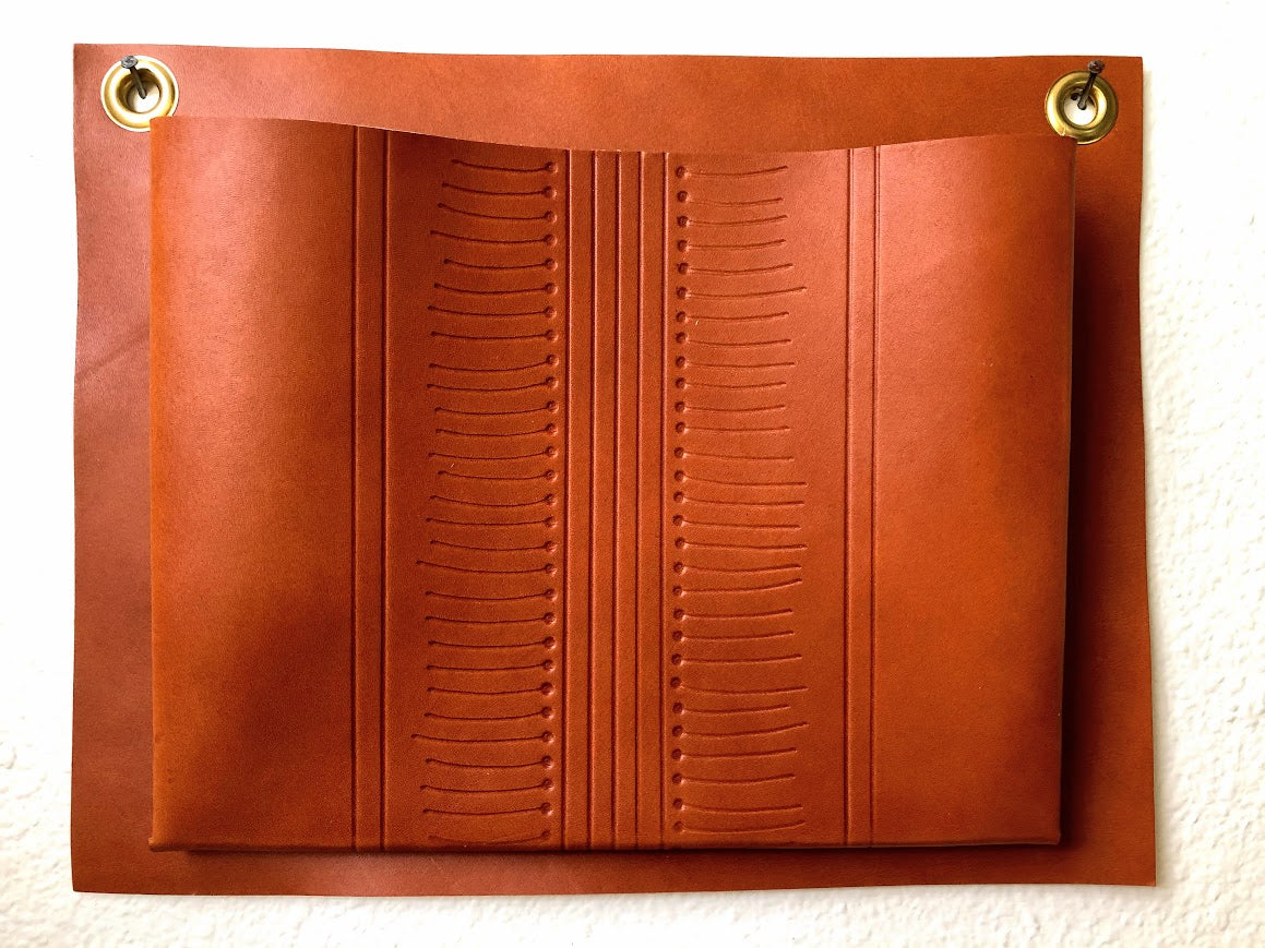Tan, patterned, leather wall pocket hanging on wall.