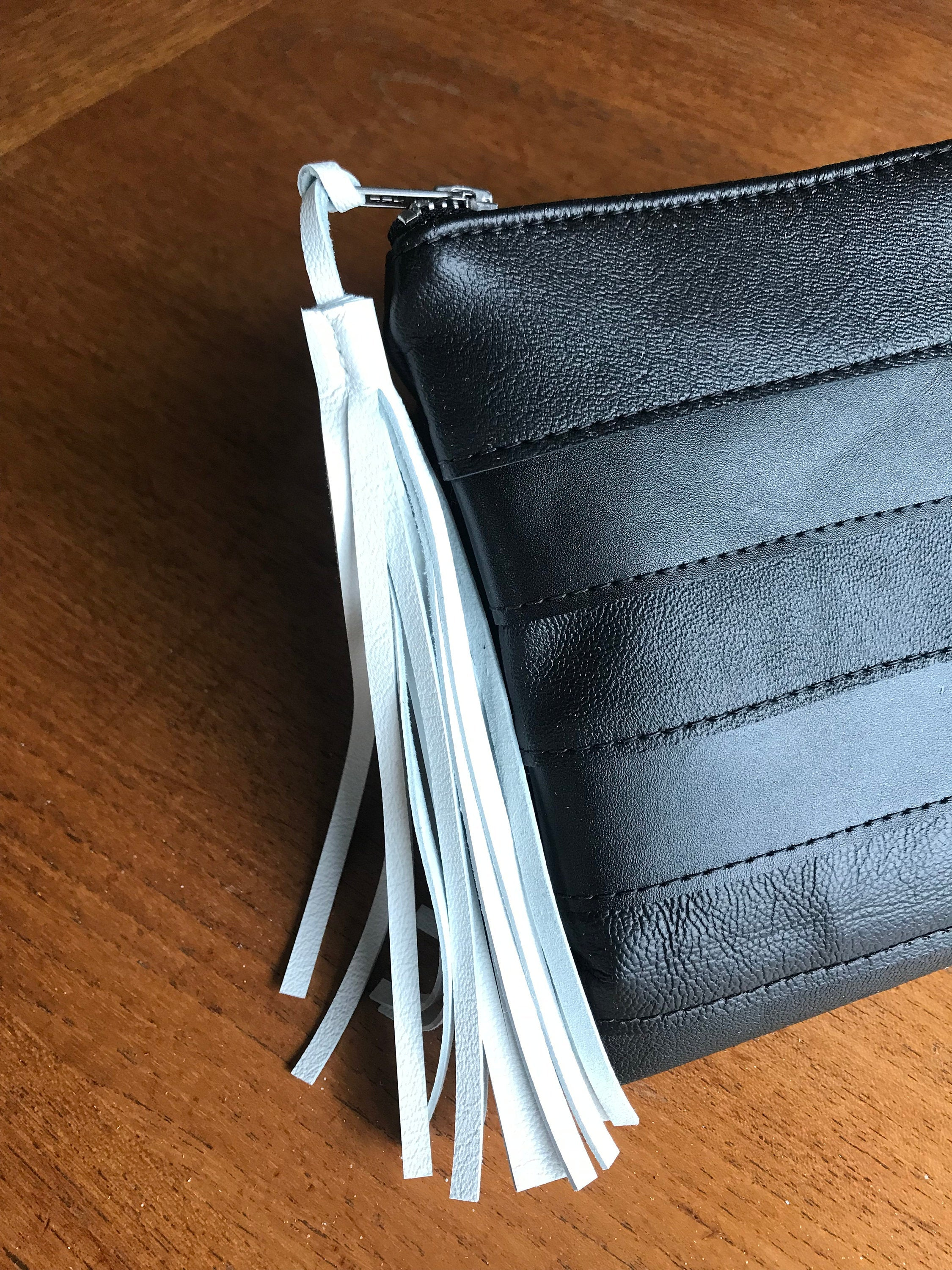 White leather tassel shown on black leather clutch