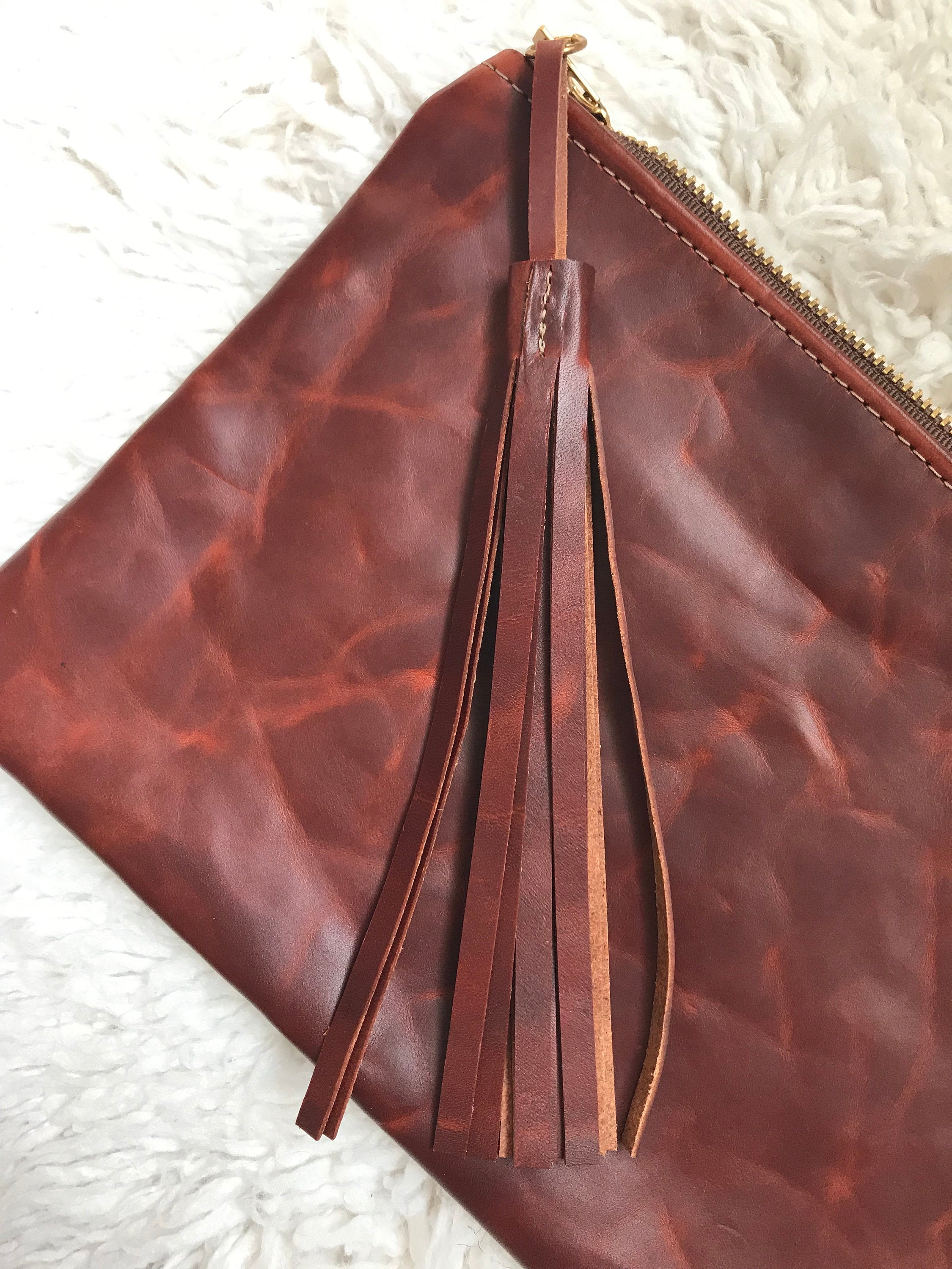 Brown leather tassel on distressed leather clutch bag