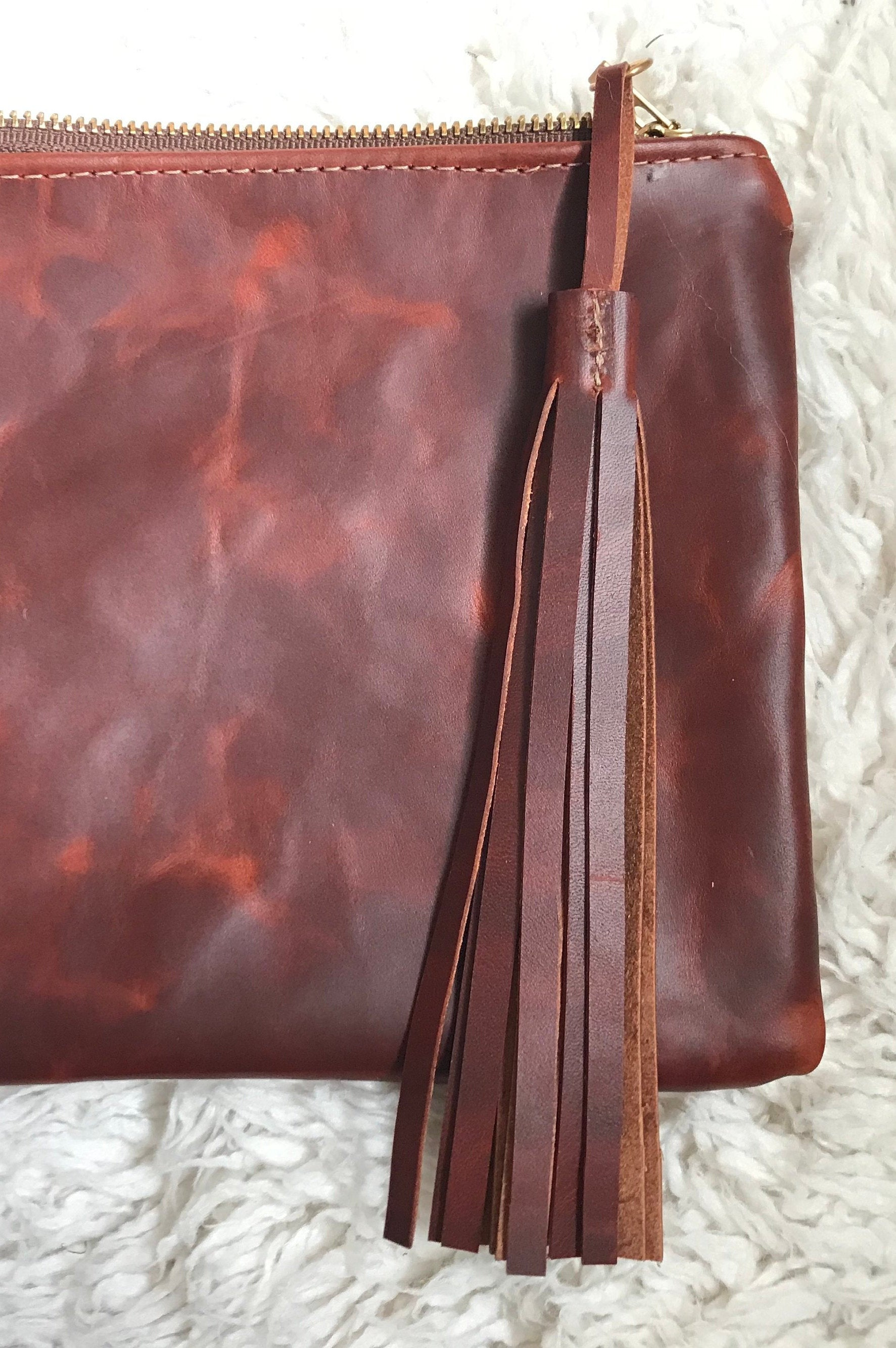 Red brown oiled leather tassel shown attached to clutch purse