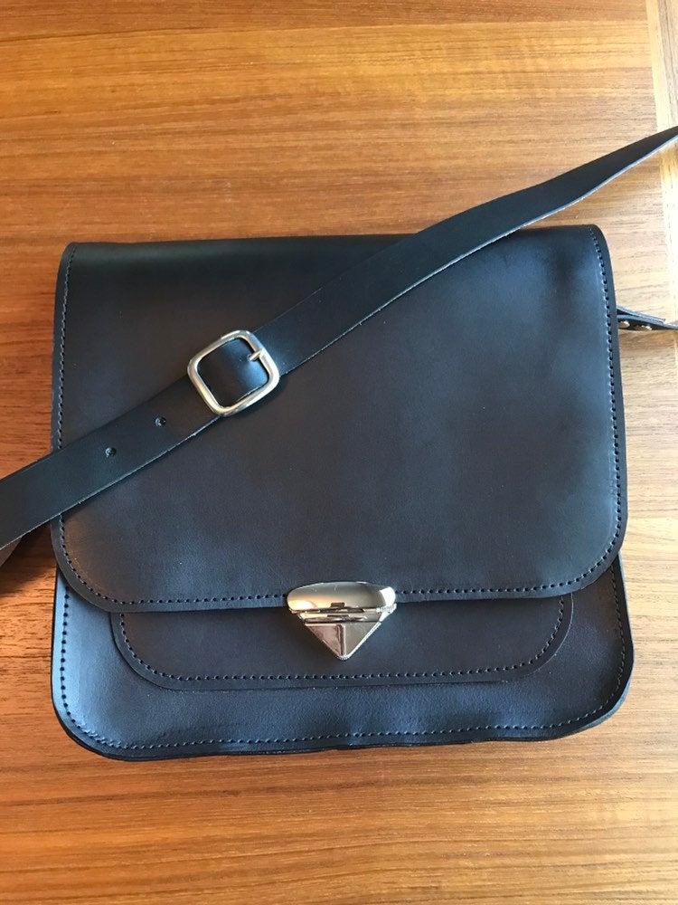 Structured black leather crossbody messenger bag lies on table