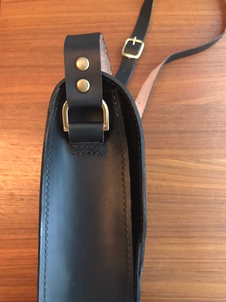 Side view of structured black crossbody bag showing strap hardware