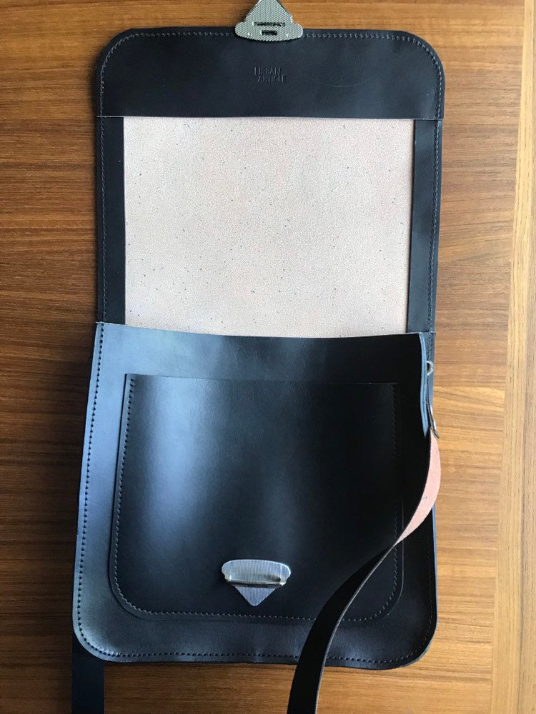 Black leather crossbody bag is flapped open on table showing interior pocket and triangle clasp