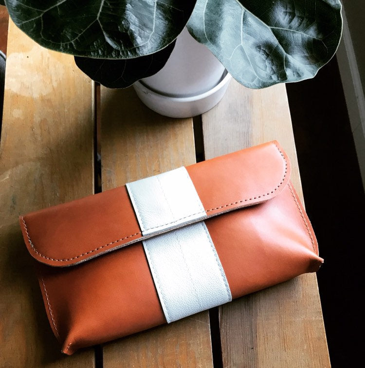 Tan leather foldover clutch with white stripe sits on table under green leaves