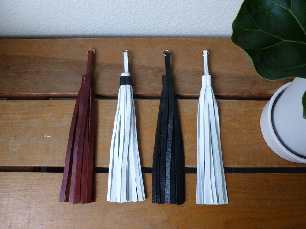 Four leather tassels laid side by side on a table near a plant. Brown, black and white, black, white.
