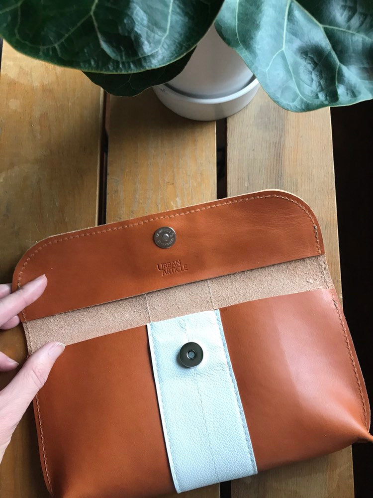 Hand opens tan leather clutch showing unlined interior, magnetic clasp, and Urban Article logo. Purse on a table with plant