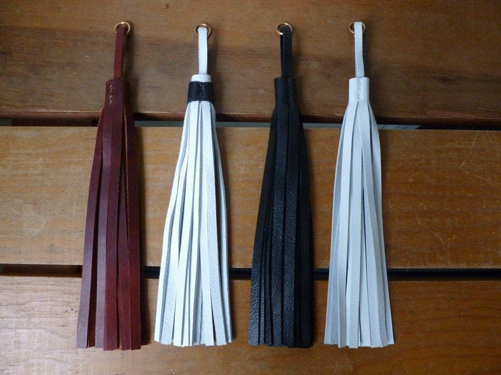 Four leather tassels with jump rings lie on a table. Brown, white with black wrap, black, and white