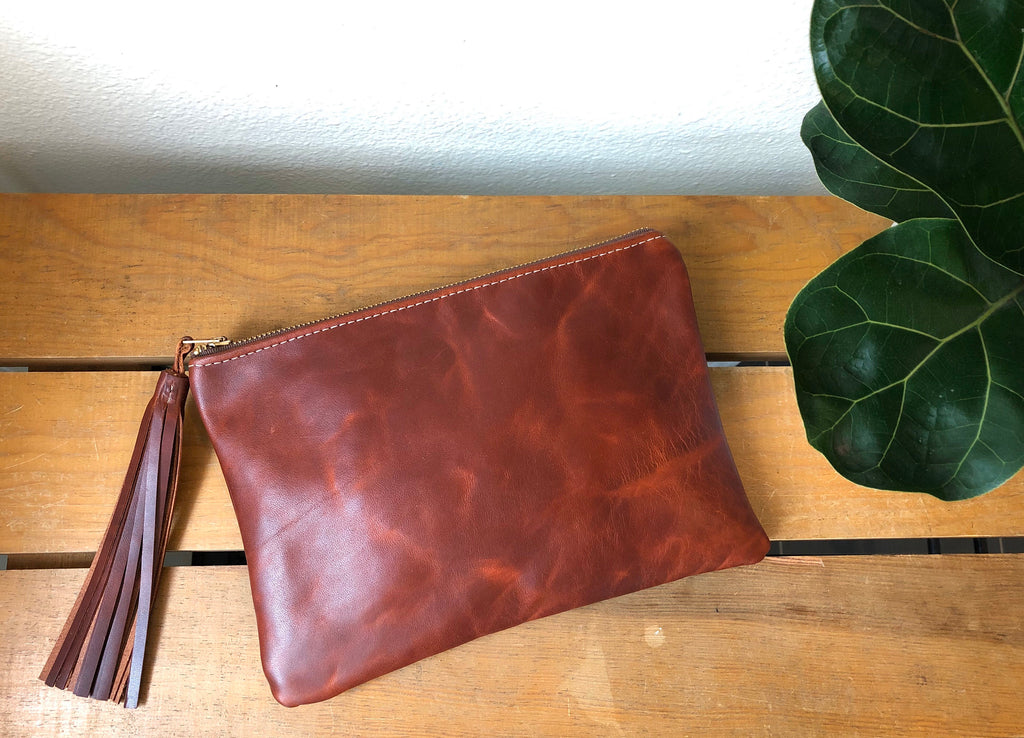Red brown distressed leather clutch with tassel lying on wood table near green plant