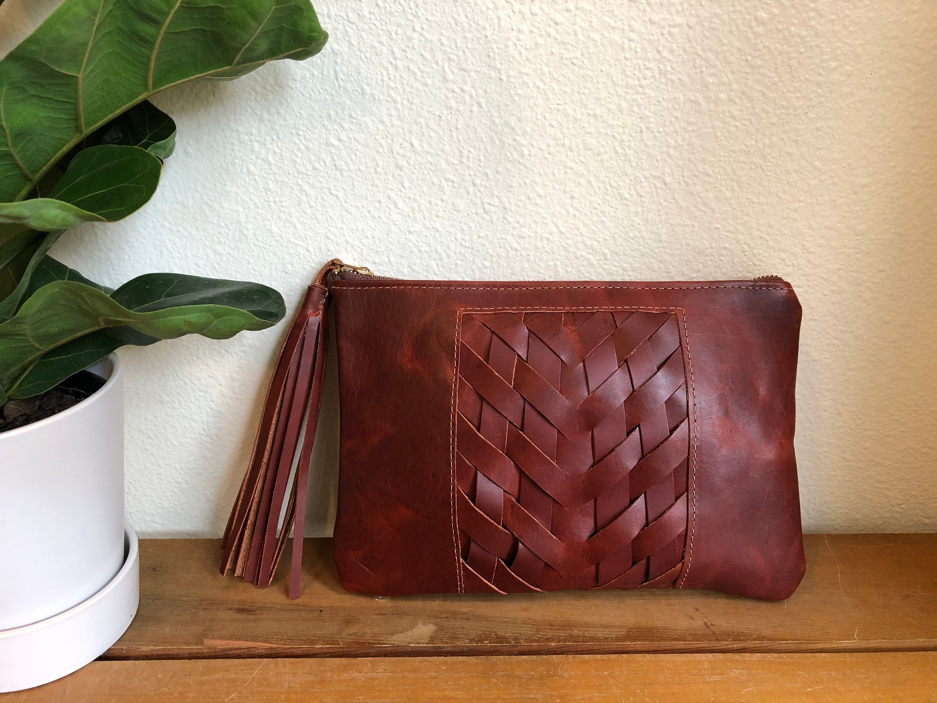 Brown leather clutch bag with woven panel and tassel sits near plant on table