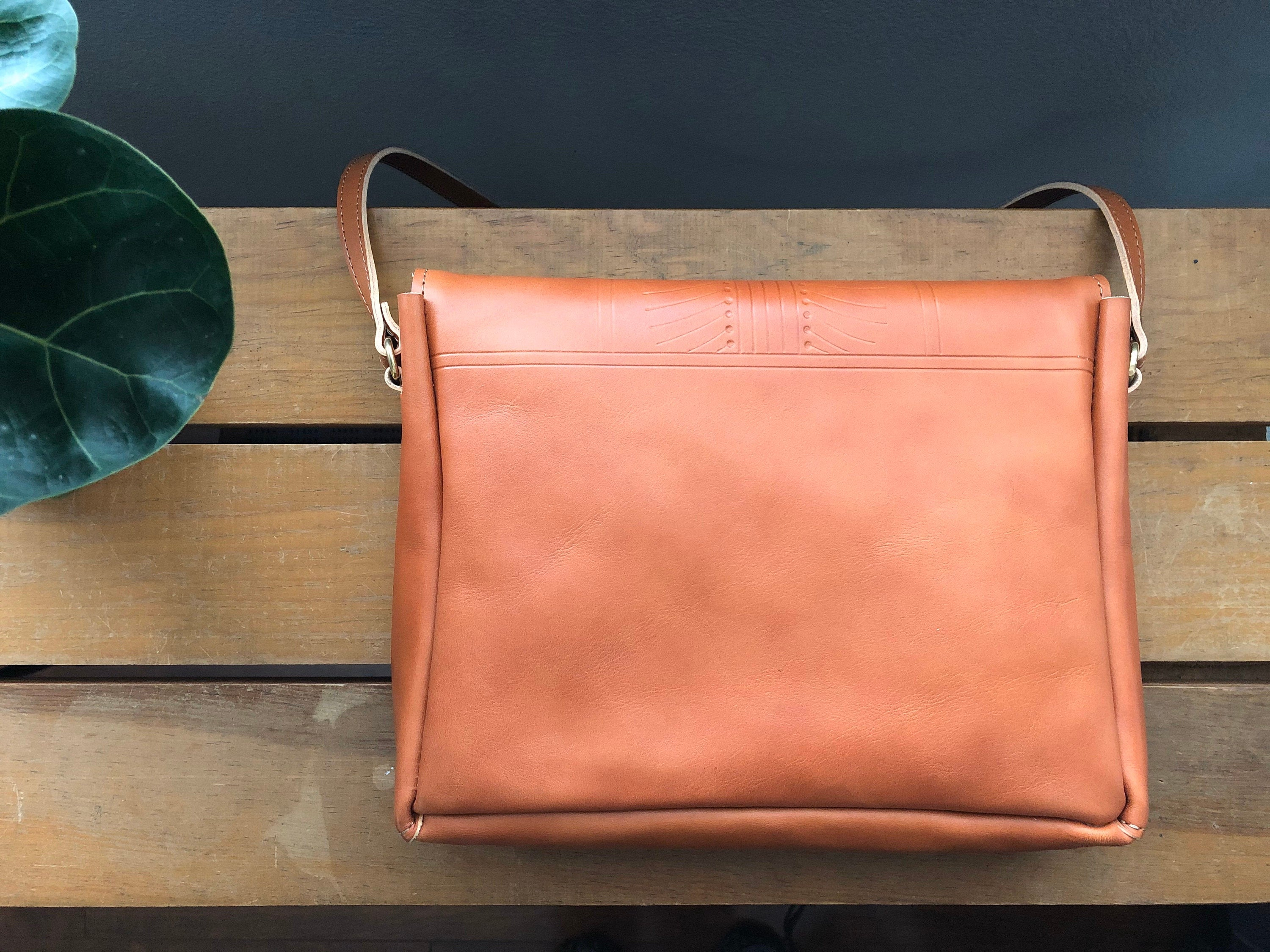 Back of tan leather crossbody bag with small tooling detail. Resting on table near plant