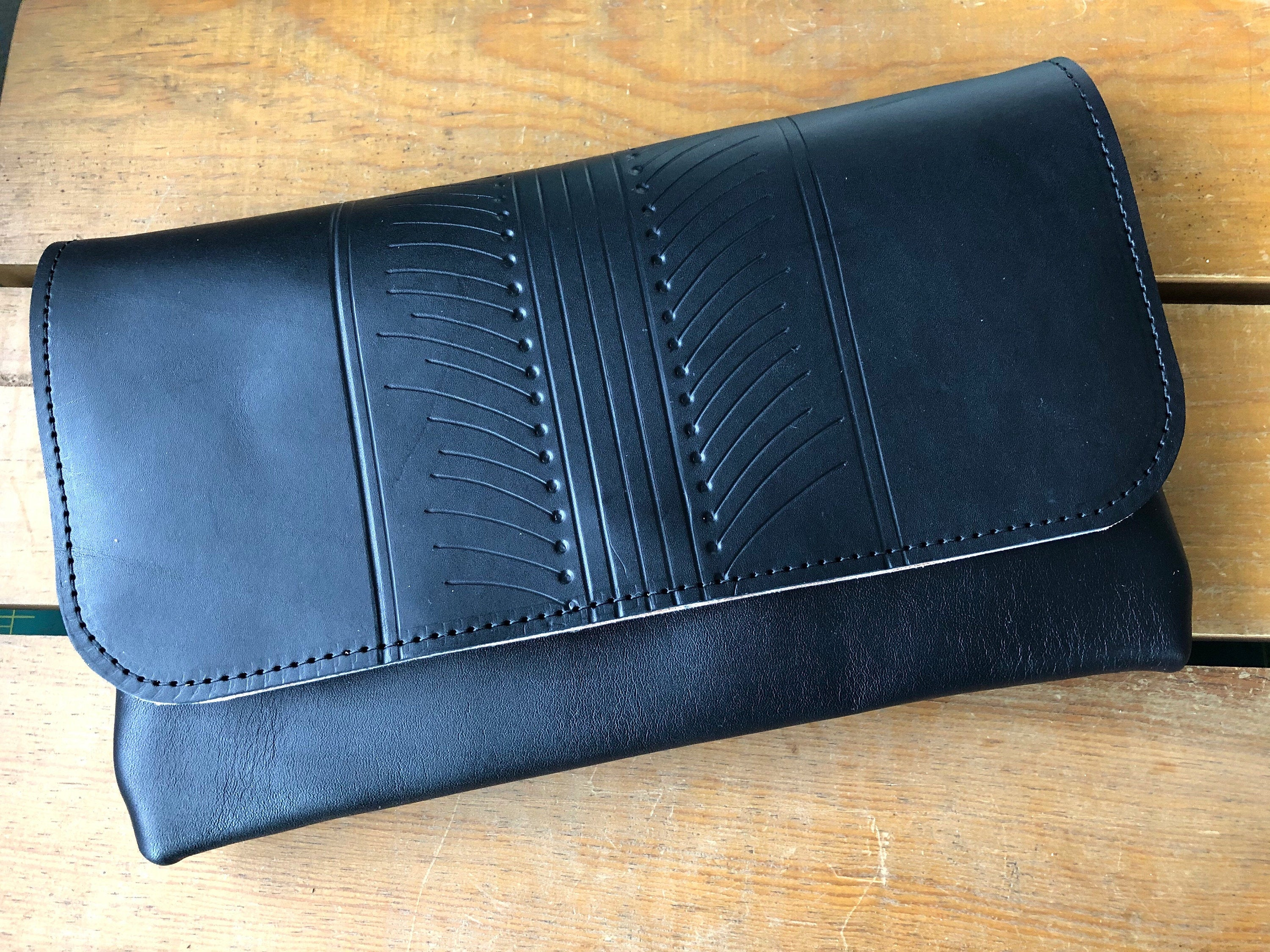 Black leather clutch with patterned design on front, sitting on a table