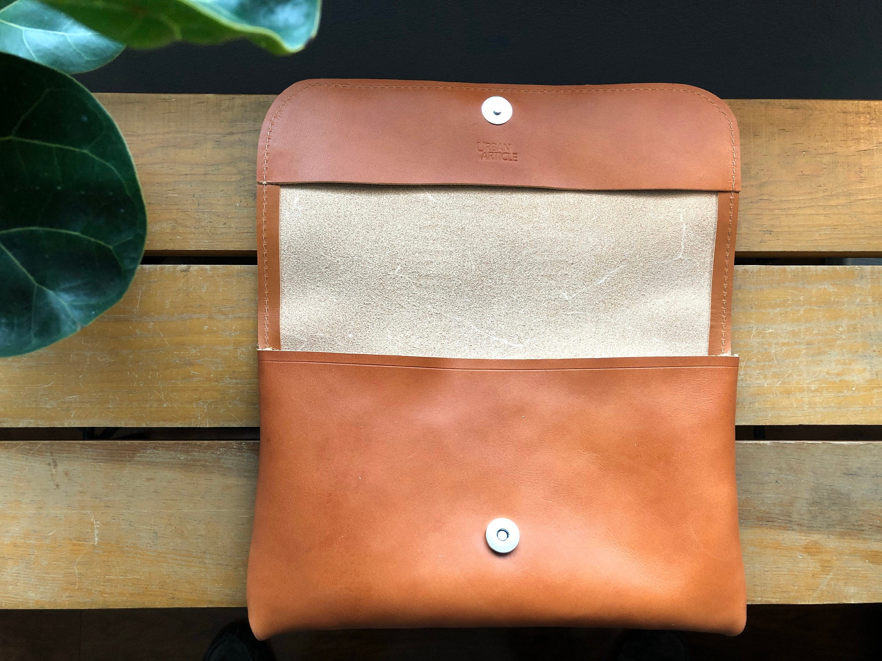 Tan leather clutch opened to see natural leather interior and magnetic clasp