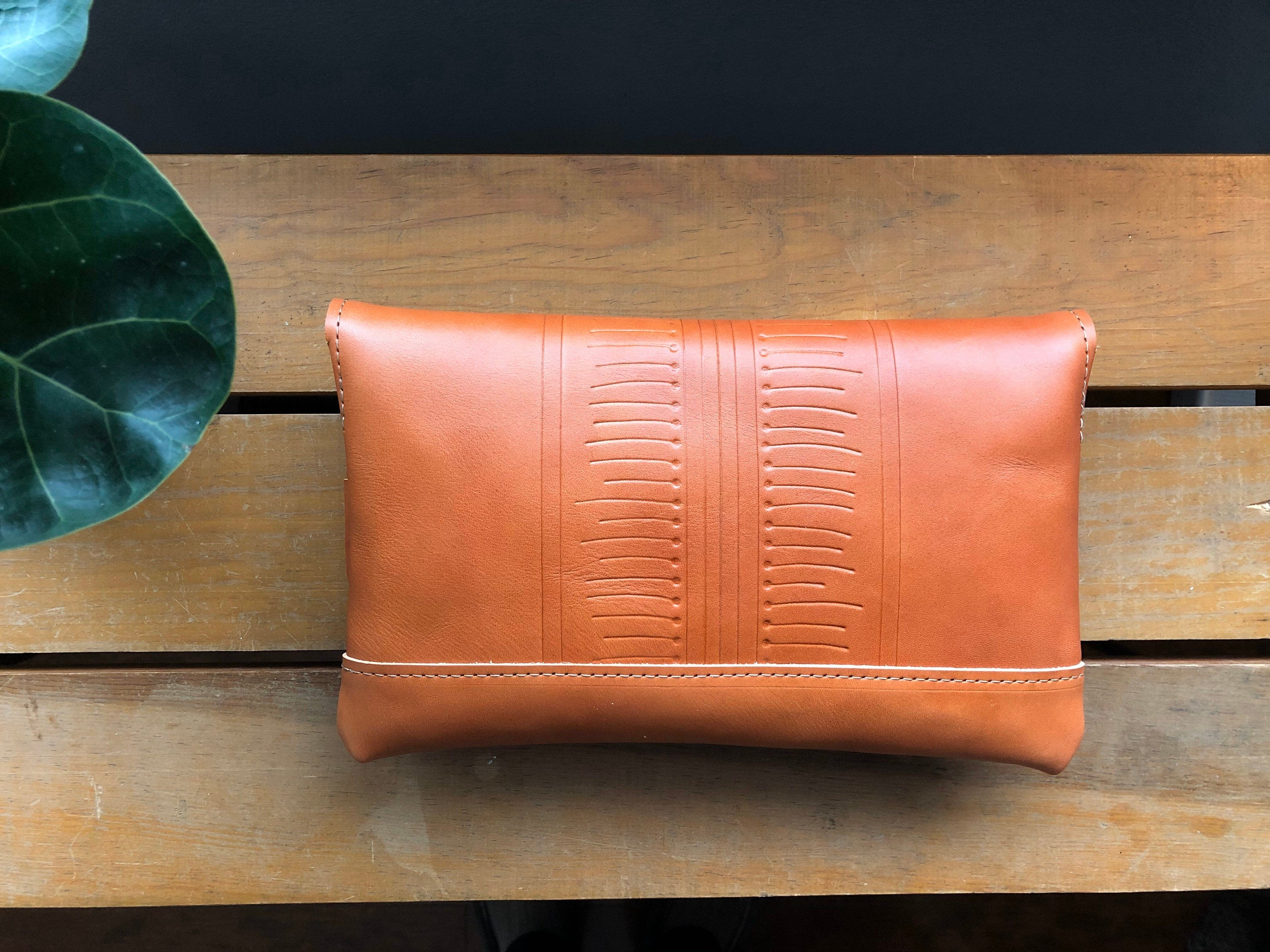 Back view of tan leather clutch with patterned detail sitting on wooden table near plant