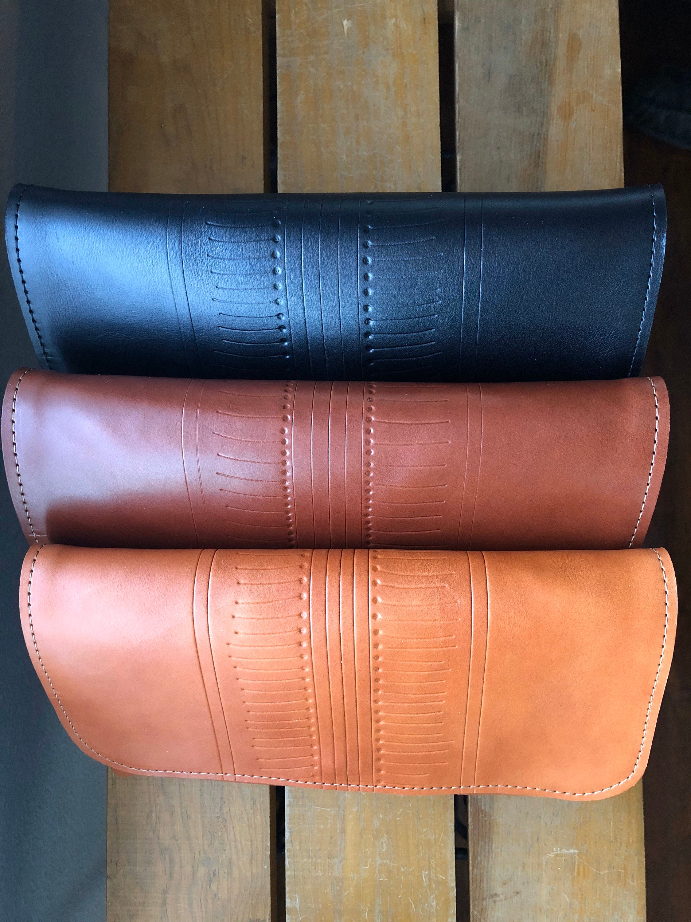 Row of three leather clutches, black, brown, and tan.
