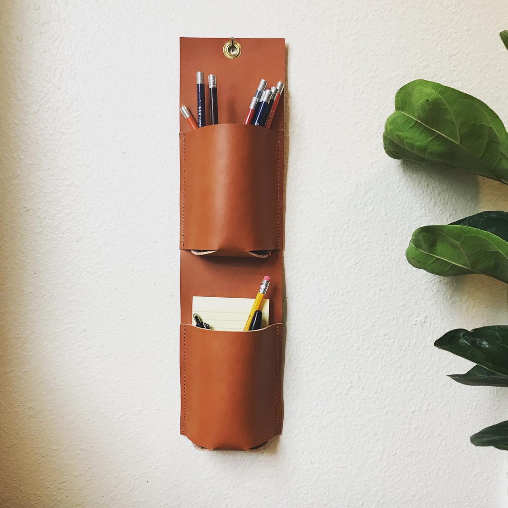 Vertical leather wall organizer with two pockets holding colored pencils, pens, and post it notes